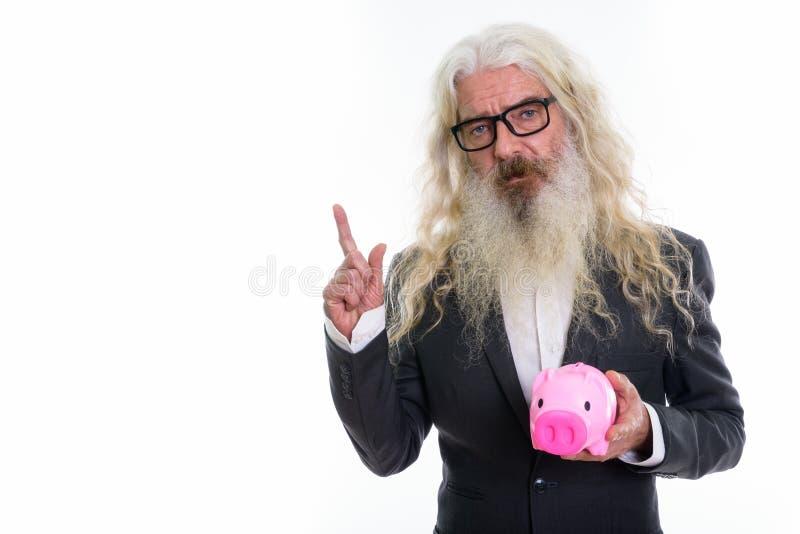 El estudio tiró del hombre de negocios barbudo mayor que sostenía whi de la hucha imágenes de archivo libres de regalías