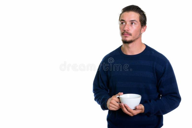 El estudio tiró del hombre hermoso joven que sostenía la taza de café mientras que piense fotografía de archivo libre de regalías