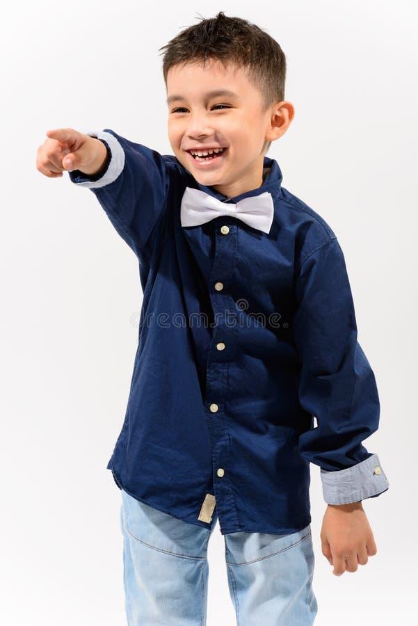 El estudio tiró del muchacho feliz lindo que sonreía y que reía mientras que pointin fotografía de archivo libre de regalías