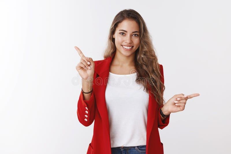 El estudio tiró a la mujer feliz sonriente amistosa atractiva del caucásico 25s que llevaba la chaqueta roja que señalaba de lado imagen de archivo