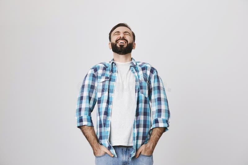 El estudio tirado de adulto europeo hermoso con la barba y el bigote, riendo hacia fuera ruidosamente, se inclinó detrás, llevand imagen de archivo