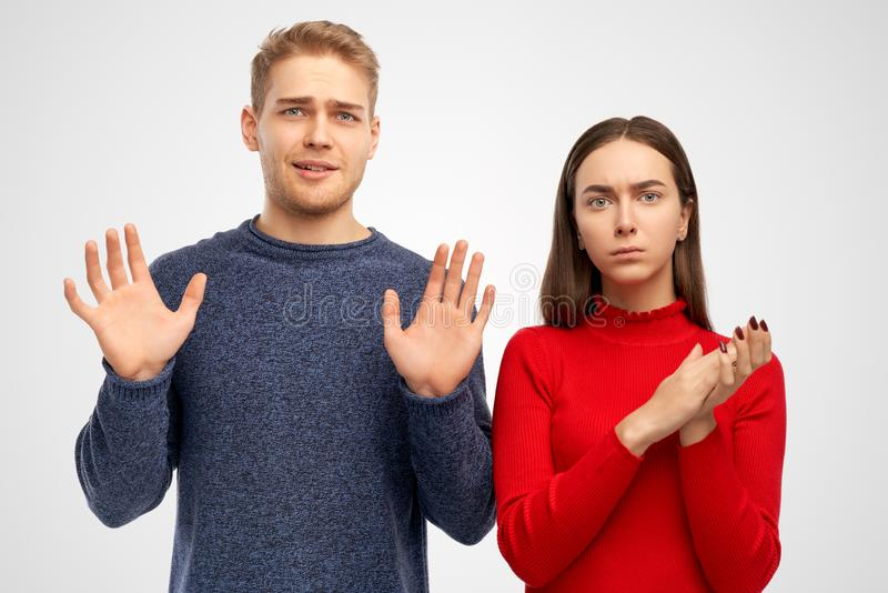 El estudio tirado de gente joven gruñona con la expresión irritada, hace gesto de la parada y mantiene las palmas frente, pide pa fotografía de archivo