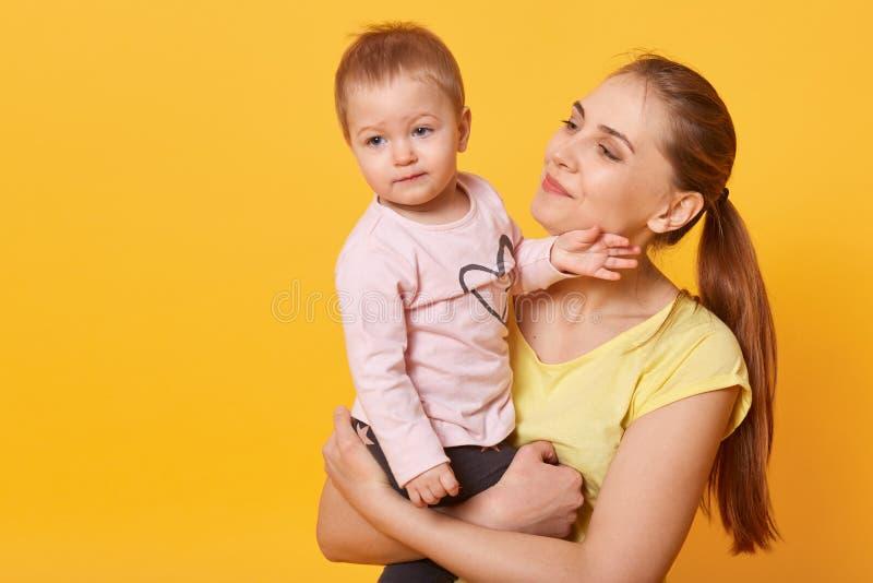 El estudio tirado de la madre cari?osa que celebra a su beb?, ni?o que mira a un lado, mam? admira su doughter encantador aislado fotos de archivo