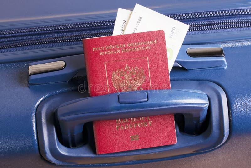 El euro y el pasaporte ruso con una maleta azul, alistan para un viaje del negocio o del día de fiesta en el extranjero foto de archivo libre de regalías