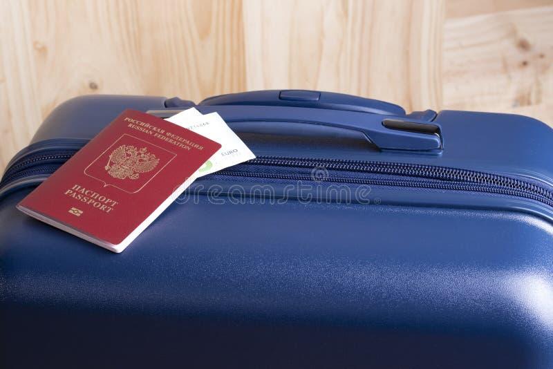 El euro y el pasaporte ruso con una maleta azul, alistan para un viaje del negocio o del día de fiesta en el extranjero imagen de archivo libre de regalías