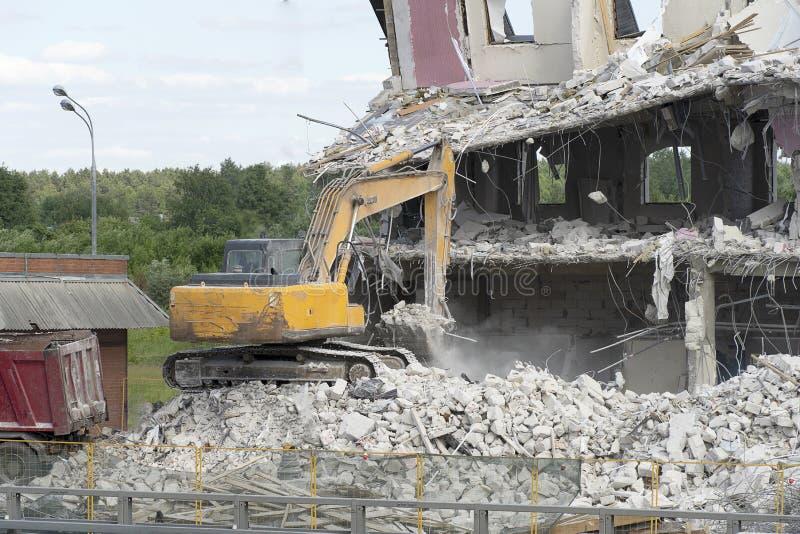 El excavador amarillo coge la basura de la construcción para cargar sobre un camión La técnica destruyó el edificio, es refuerzo, fotografía de archivo