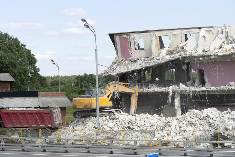 El excavador amarillo coge la basura de la construcción para cargar sobre un camión La técnica destruyó el edificio, es refuerzo, fotos de archivo
