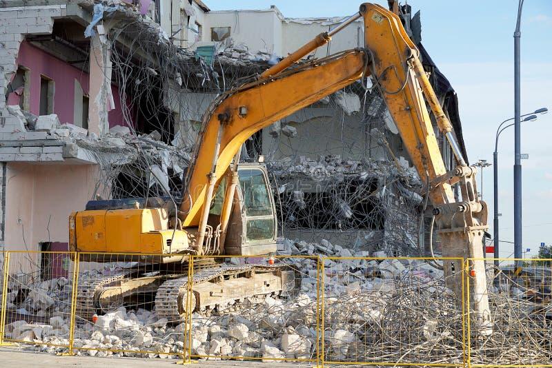 El excavador amarillo demuele un edificio de varios pisos con una herramienta Los pisos destruidos del edificio, son pedazos de p foto de archivo libre de regalías