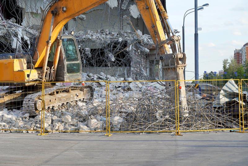 El excavador amarillo destruyó un edificio de varios pisos con una herramienta del cincel El equipo destruye el edificio, colocac imagen de archivo libre de regalías
