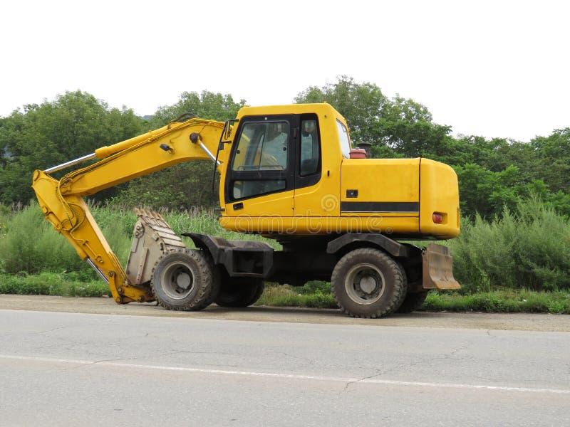 El excavador amarillo parqueó en el borde de la carretera en el fondo verde de maderas fotografía de archivo