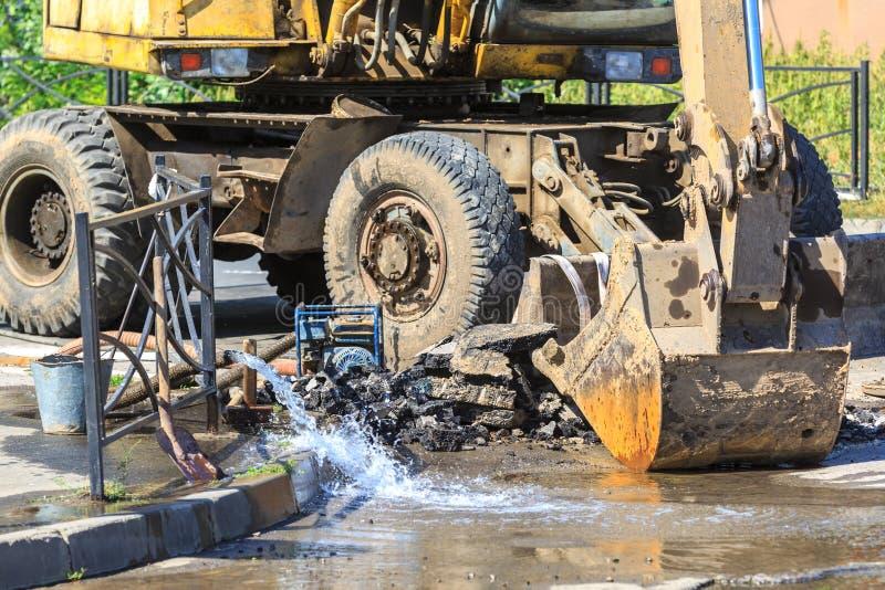 El excavador ayuda a eliminar el problema de romper un tubo en la calle en un día de verano caliente fotos de archivo libres de regalías