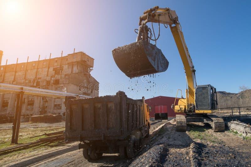 El excavador carga los aceites minerales en el camión imagenes de archivo