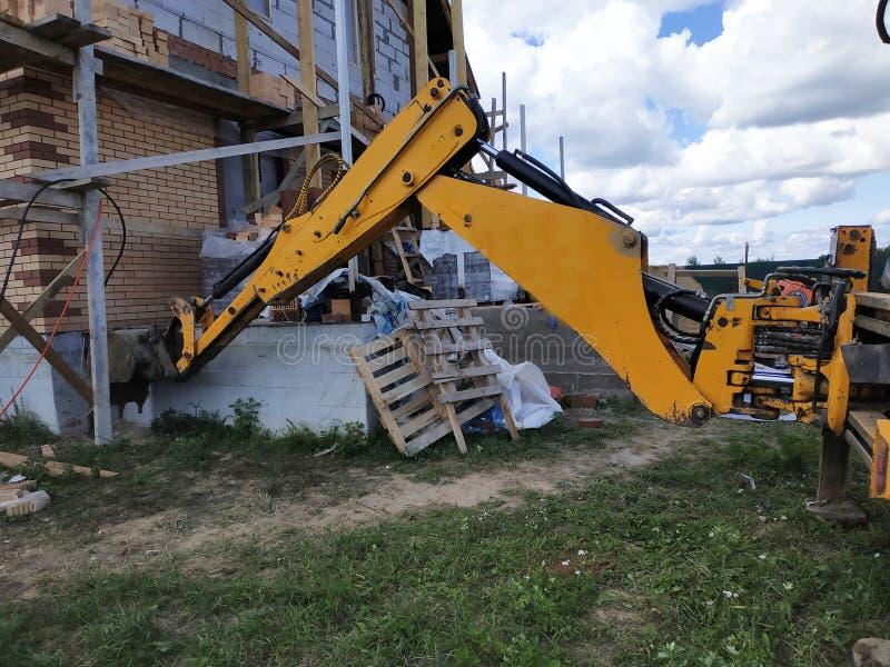 El excavador cava un dardo alrededor de un edificio que esté bajo construcción fotografía de archivo libre de regalías