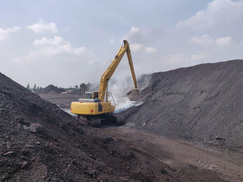 El excavador extinguir los fuegos de la combustión espontánea del carbón fotos de archivo libres de regalías