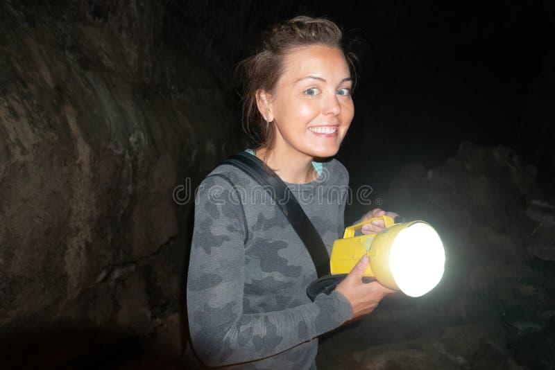 El explorador feliz de la mujer sostiene una linterna mientras que excava y spelunking el metro en Lava Beds National Monument en imagen de archivo libre de regalías