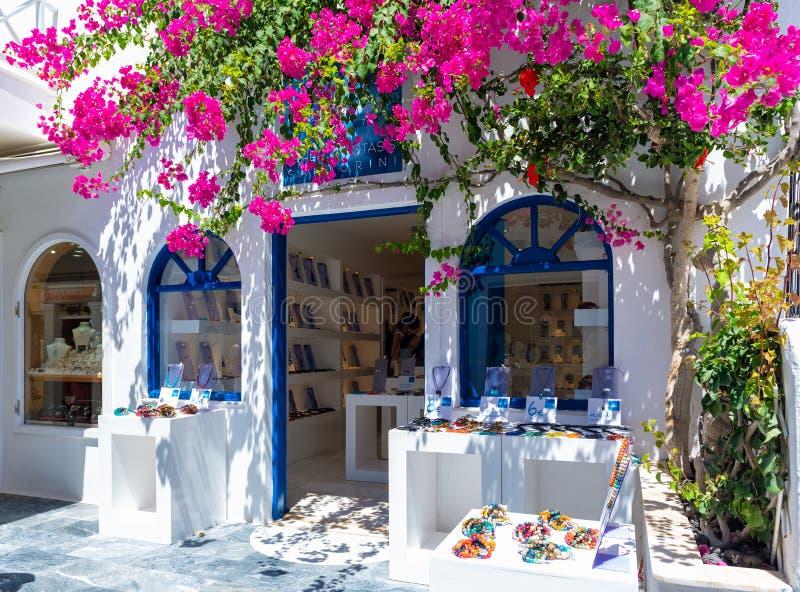 El exterior hermoso de la tienda de souvenirs, adornado con la buganvilla púrpura florece en la isla de Santorini foto de archivo libre de regalías