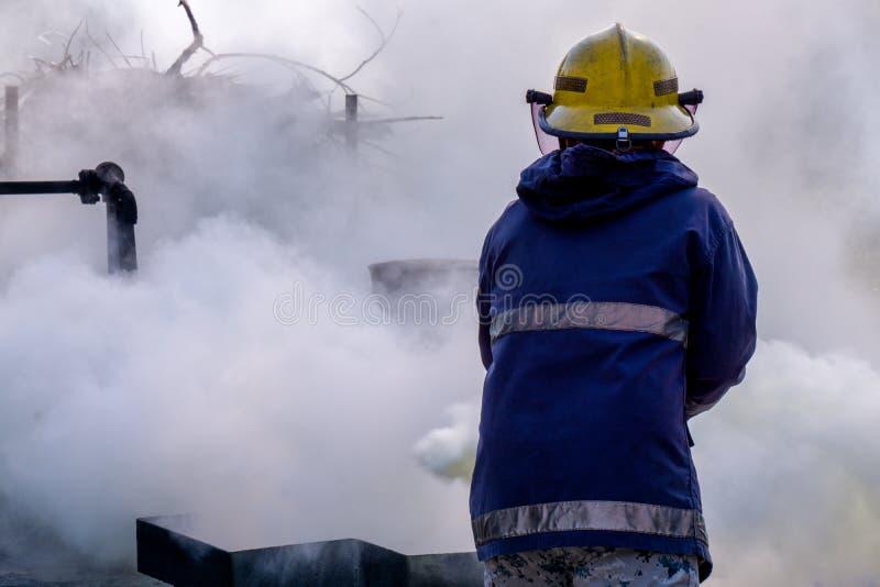El extintor del dióxido de carbono del CO2 del uso del bombero para extinguir un fuego crea el humo blanco y se vaporiza foto de archivo libre de regalías