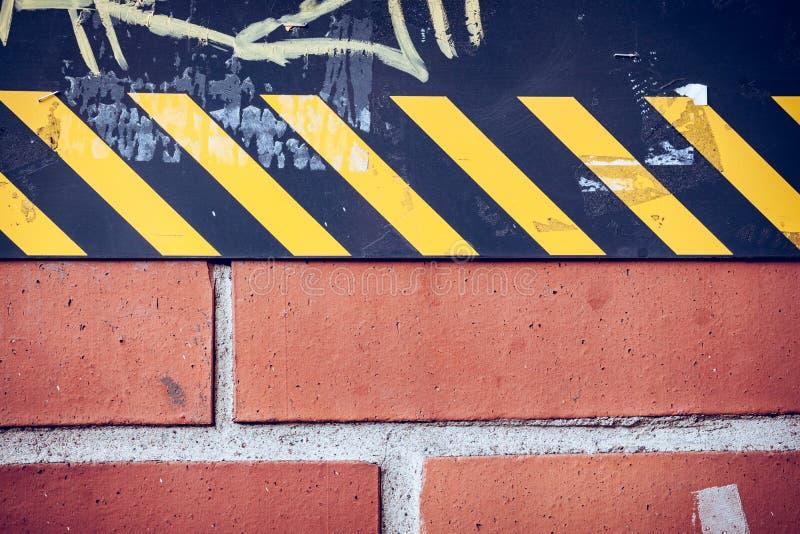 El extracto de la pared en calle de la ciudad con cautela raya imagenes de archivo