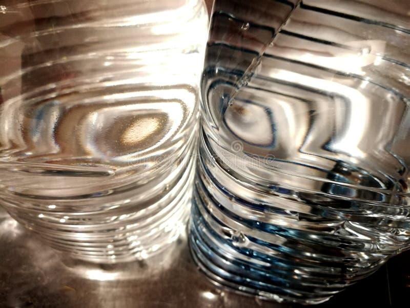 El extracto forma el agua embotellada que filtra la luz en gris, azul y blanco imágenes de archivo libres de regalías