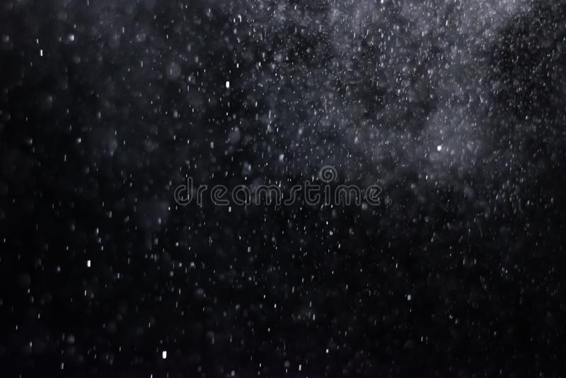 El extracto salpica del agua en un fondo negro fotografía de archivo