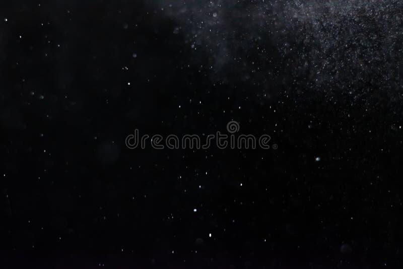 El extracto salpica del agua en un fondo negro foto de archivo