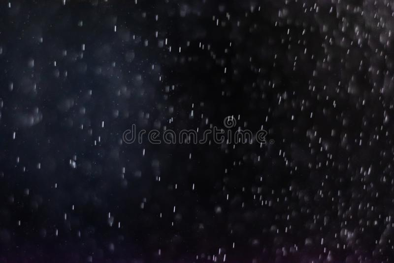 El extracto salpica del agua en un fondo negro imagenes de archivo