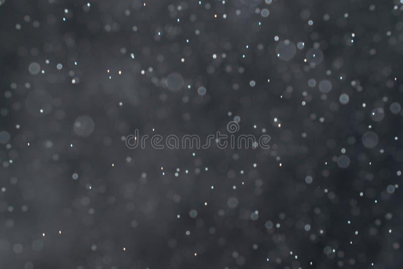 El extracto salpica del agua en un fondo negro imagen de archivo