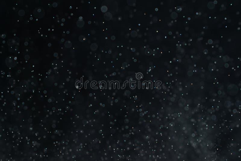 El extracto salpica del agua en un fondo negro fotos de archivo libres de regalías