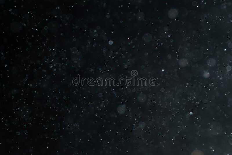 El extracto salpica del agua en un fondo negro fotografía de archivo libre de regalías