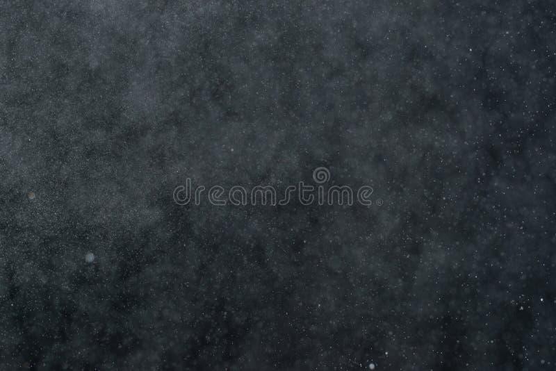 El extracto salpica del agua en un fondo negro imágenes de archivo libres de regalías
