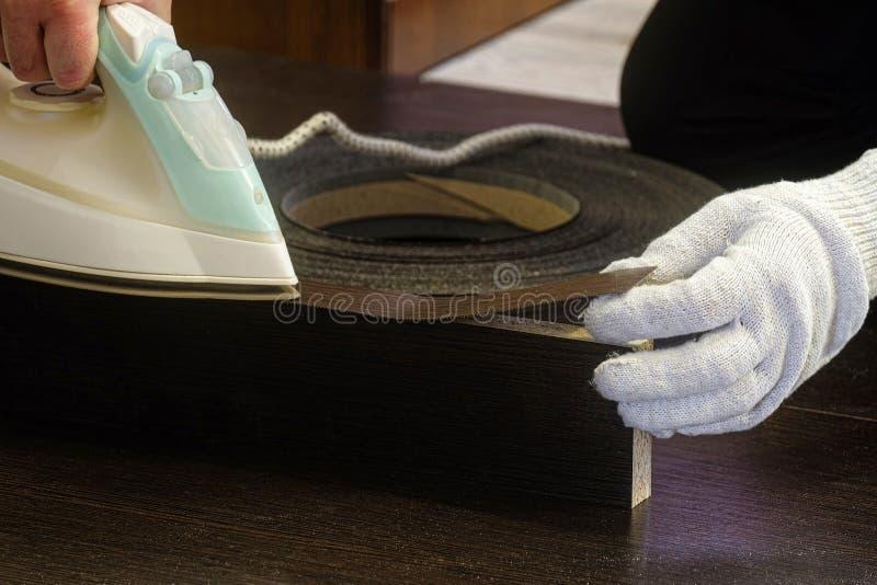 El fabricante de los muebles pega el borde de la melamina a la hoja laminada del conglomerado foto de archivo libre de regalías