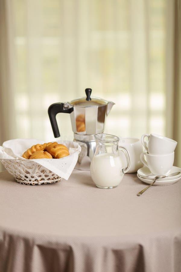 El fabricante, las tazas y los cruasanes de café en la cesta están en un t redondo imagen de archivo