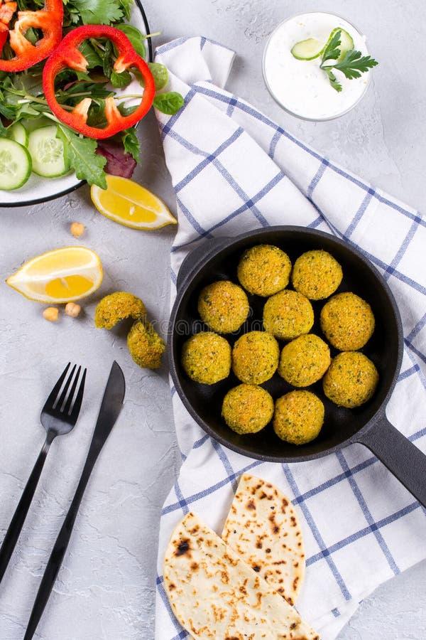 El falafel hecho en casa de Oriente Medio tradicional de los platos, pita, sirvió con las verduras y las especias en la tabla con foto de archivo