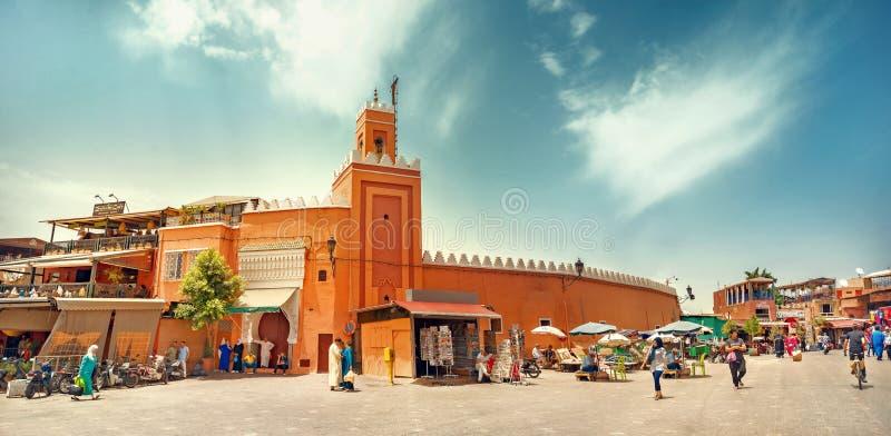 EL famoso Fna de Djemaa do mercado com mesquita e minarete no quarto do medina de C4marraquexe C4marraquexe, Marrocos fotografia de stock