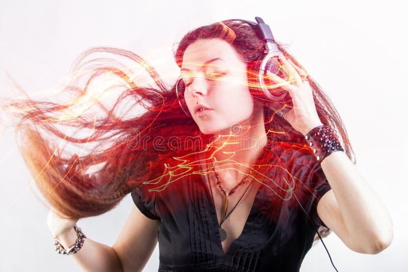 El fan de la muchacha canta y baila escuchar la m?sica La mujer morena joven en auriculares grandes disfruta de m?sica foto de archivo libre de regalías
