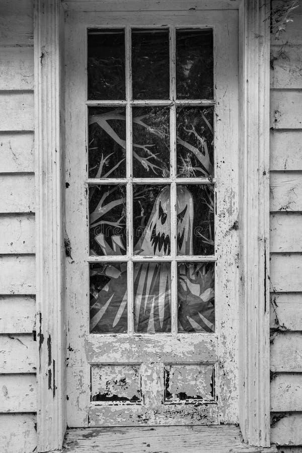 El fantasma pintado mira a través de la puerta de la casa vieja del funcionamiento abajo fotografía de archivo libre de regalías