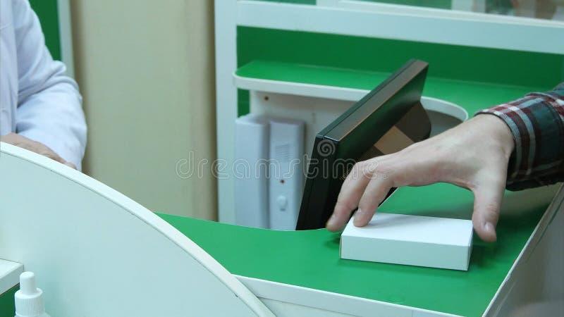 El farmacéutico que sostenía las tabletas en manos y las dio al cliente, que pagan con efectivo de los dólares imagenes de archivo