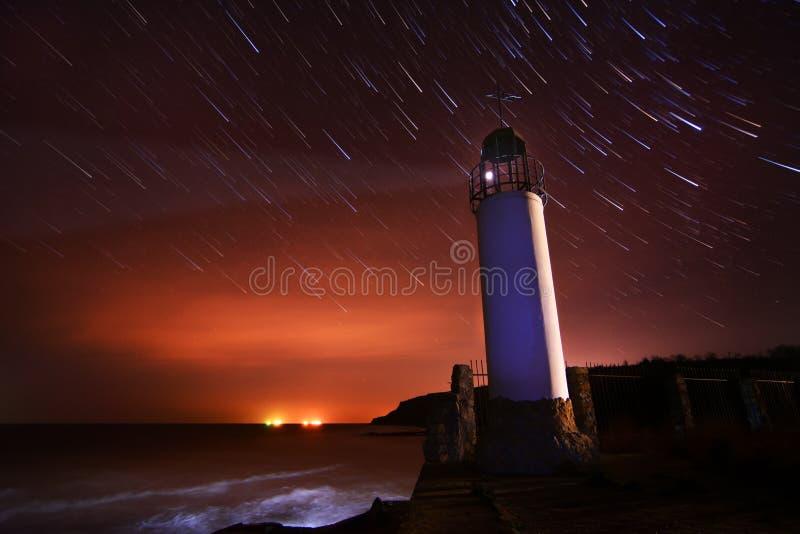 El faro con el cielo nocturno en el fondo protagoniza trai fotos de archivo libres de regalías