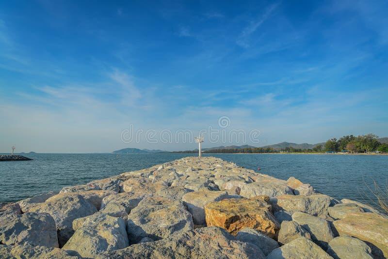 El faro en la isla adyacente al borde del mar y al cielo hermoso fotografía de archivo