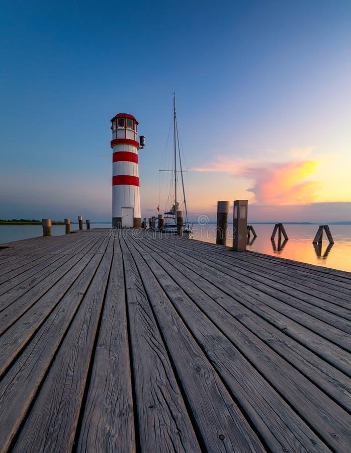 El faro en el lago Neusiedl, Podersdorf ve, Burgenland, Austria Faro en la puesta del sol en Austria Embarcadero de madera con el foto de archivo