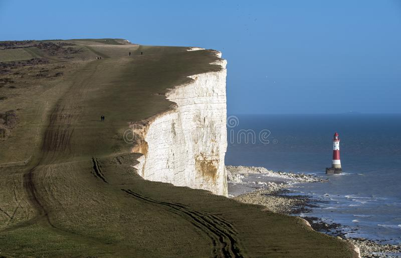 El faro y los acantilados de tiza principales con playas famosos cerca de Eastbourne en Sussex del este, Inglaterra fotos de archivo