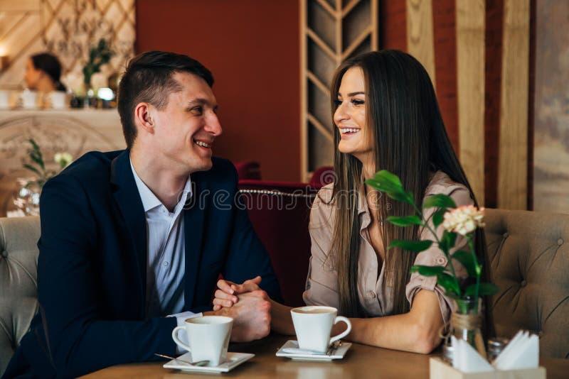 El fechar en el café Pares jovenes hermosos que se sientan en el café, amor de consumición del café, fechando fotografía de archivo libre de regalías