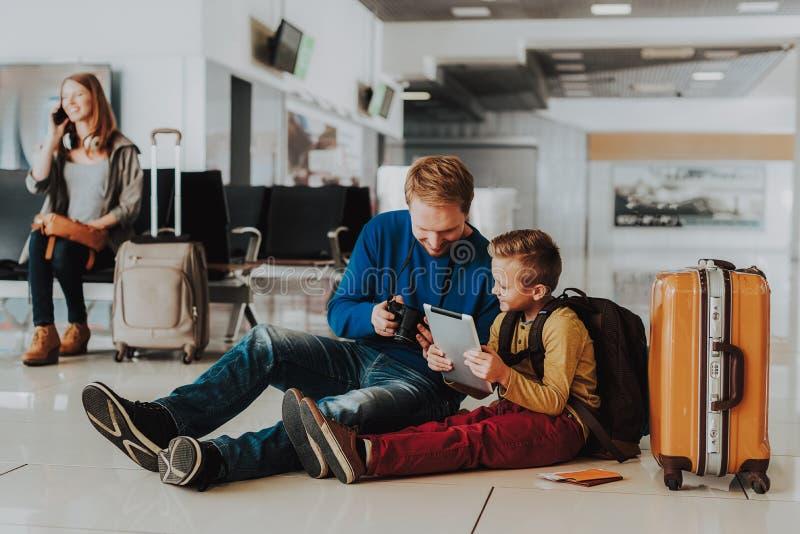 El felices papá e hijo están utilizando los dispositivos modernos en el aeropuerto imagen de archivo