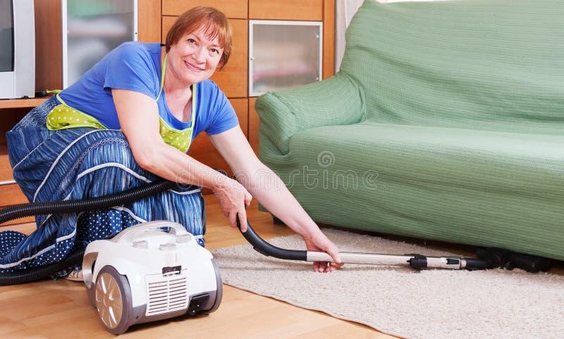 El feliz limpiar con la aspiradora maduro de la mujer imagen de archivo