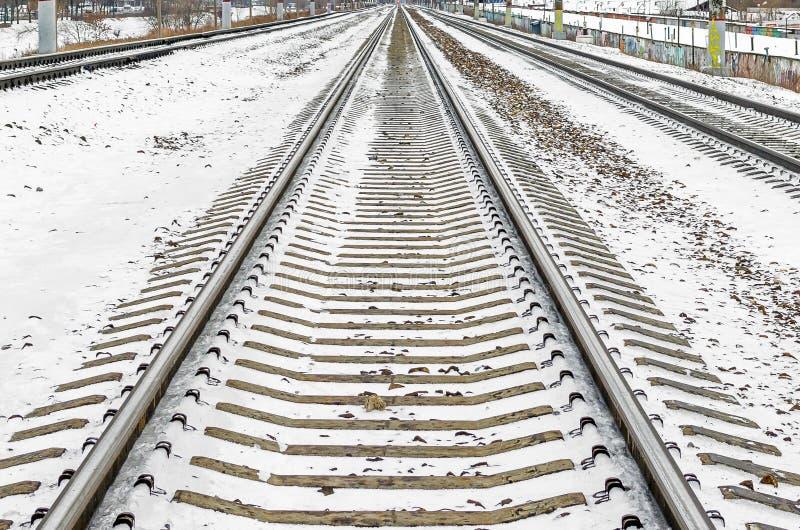El ferrocarril cerca nieve ausente de los durmientes con barandilla en invierno imagenes de archivo