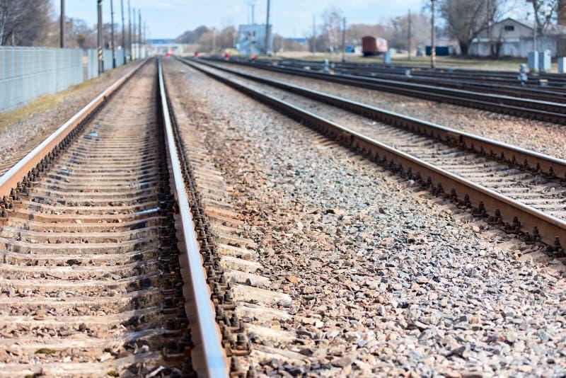 El ferrocarril del foco selectivo va todo derecho en el d3ia soleado de la primavera al fondo del horizonte de la neblina azul co imagenes de archivo