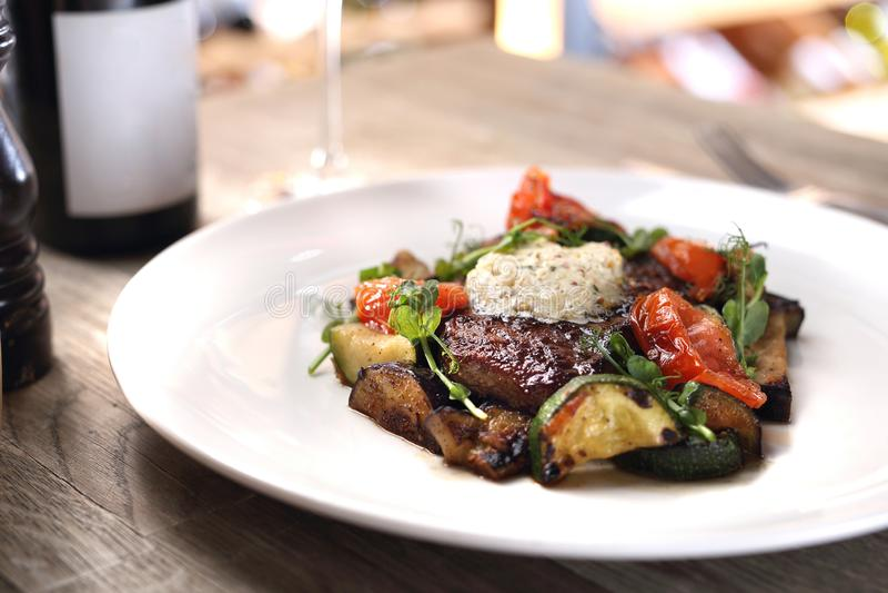El filete asado a la parrilla del bistec de costilla con mantequilla de hierba y verduras asadas a la parrilla sirvi? en una plac fotos de archivo