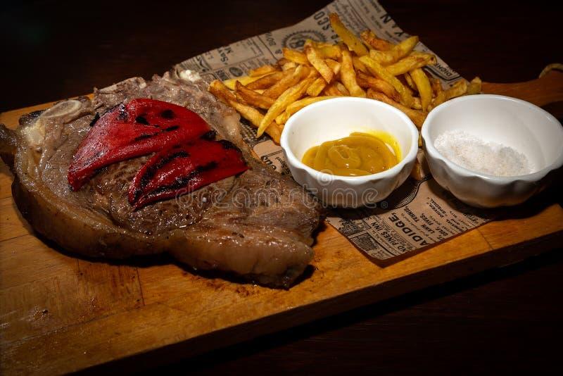 El filete de carne de vaca raro asado a la parrilla sirvió en el tablero de madera con las patatas fritas imagen de archivo
