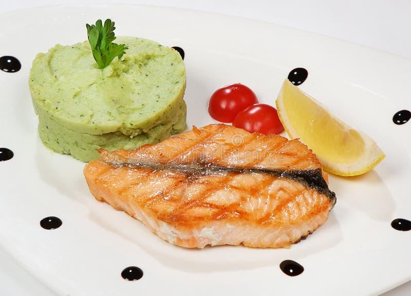El filete de color salmón sirvió con los tomates de los purés de patata, del bróculi y de cereza fotografía de archivo libre de regalías