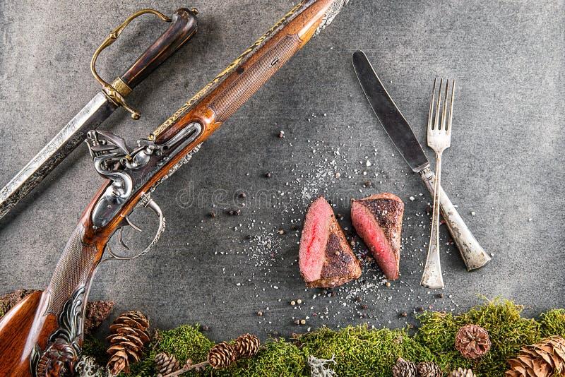 El filete de los ciervos o de la carne de venado con el arma, los cubiertos y los ingredientes largos antiguos le gusta la sal y  imágenes de archivo libres de regalías